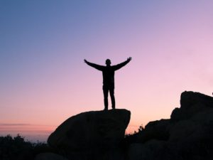 man on top of a mountain signifying success